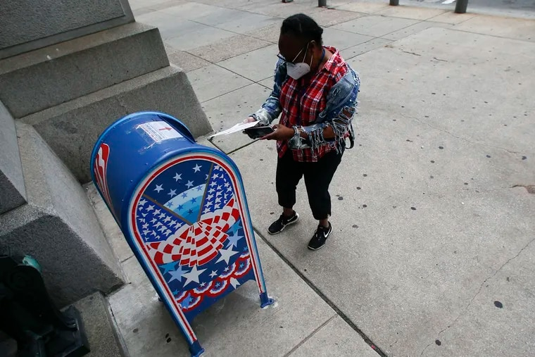 In this file photo, a voter prepares to drop off a ballot at a drop box outside Philadelphia City Hall on May 28, 2020.