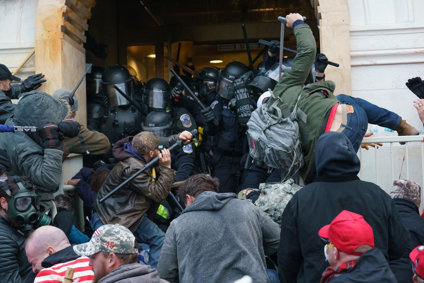 Supporters of President Donald Trump use bats, batons, and other items during a riot as they fight police defending an entrance to the U.S. Capitol in Washington, D.C., on Jan. 6, 2021.