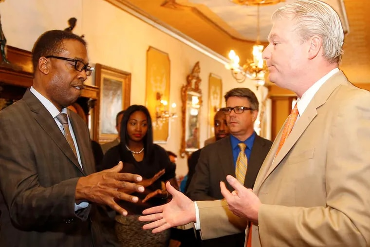 """City Council President Darrell L. Clarke (left) shakes hands with union leader John """"Johnny Doc"""" Dougherty at a fund-raiser."""