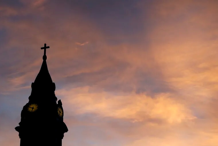 Clouds are lit by the rising sun over St. Augustine Roman Catholic Church in Philadelphia.