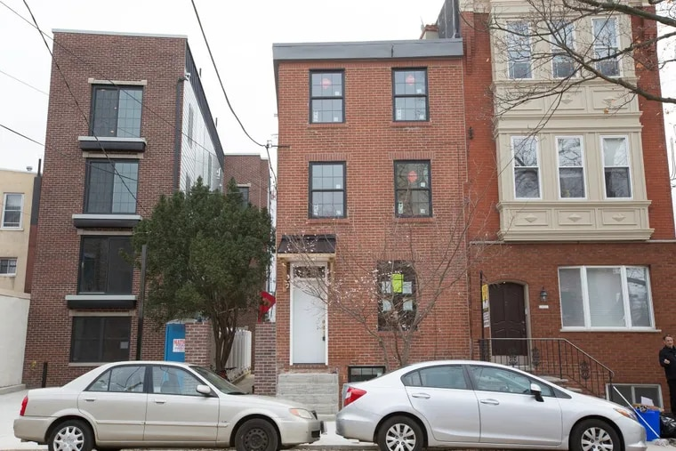 The exterior of a trinity home, center, located on the 1000 block of Moyamensing Ave., in Philadelphia.