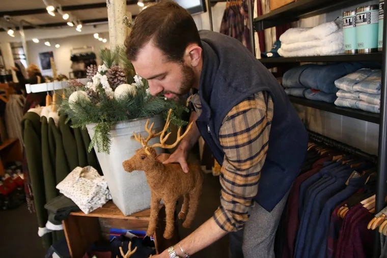 Kerran Thompson, visual manager of Village Outfitters, places a reindeer decor item on a clothing display for the upcoming Christmas season at Peddler's Village just outside New Hope.