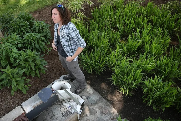 Villanova University graduate student Cara Albright stands next to a measuring station at a storm water management site near 39th Street and Girard Avenue in Philadelphia.