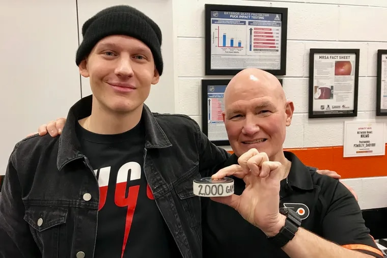 Oskar Lindblom (left) poses with athletic trainer Jim McCrossin, who was saluted for working his 2,000th professional game. Lindblom, who is undergoing treatment for Ewing's sarcoma, made a surprise visit to the Wells Fargo Center on Saturday.