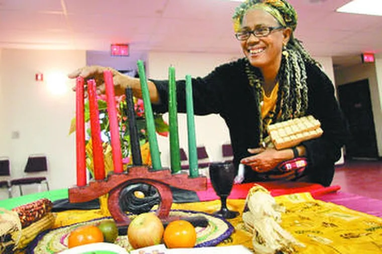 Dolores Streater-Logan adjusts candles that represent the seven Kwanzaa principles.