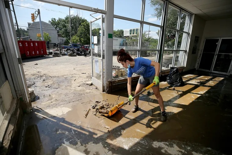 Abigael Torres helps clean the mud out of her parent's tire shop, Best Quality Tires, on Springfield Road in Darby, Pa. on August 5, 2020. Torres said flood waters from Darby Creek reached above the top of their front door.