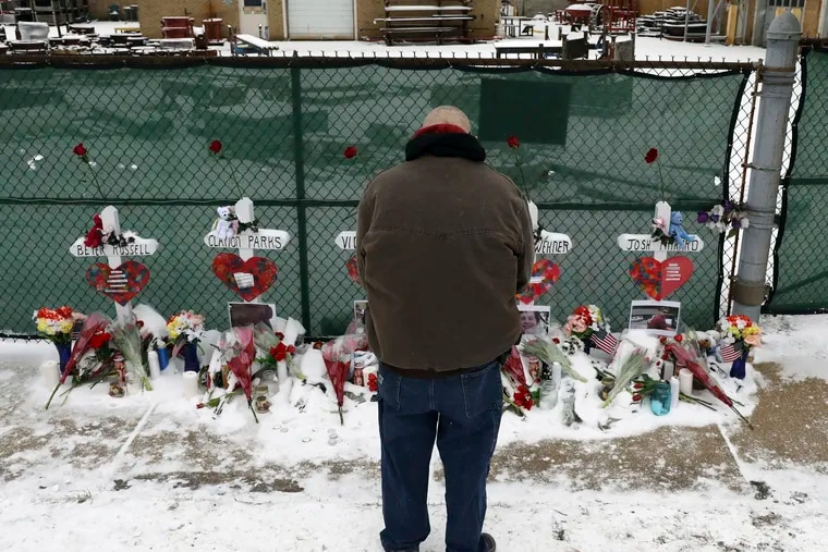 A man prays at a makeshift memorial Sunday, Feb. 17, 2019, in Aurora, Ill., near Henry Pratt Co. manufacturing company where several were killed on Friday. Authorities say an initial background check five years ago failed to flag an out-of-state felony conviction that would have prevented a man from buying the gun he used in the mass shooting in Aurora. (AP Photo/Nam Y. Huh)