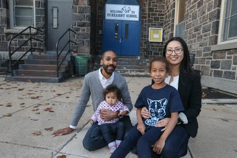 Keiko Glover and her husband Dan pose with their daughters, Maya, age 7, and Hanna, age 1, in front of the General Philip Kearny School at 6th and Fairmount streets.