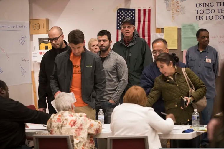 Voters sign in to vote at Trinity Episcopal Church in Ambler, Pa., on Nov. 6, 2018. The county is replacing its voting machines and hopes to have the new ones in place by the May primary, but the federal government shutdown is holding up the process. (Charles Fox/The Philadelphia Inquirer via AP)