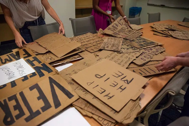 A pile of signs made by homeless people in Philadelphia and collected by Signs of Humanity sit on a table at Thomas Jefferson University on Monday, Aug. 20, 2018. Rosie Frasso and a group of students are working together with Willie Baronet to create the exhibit, which will be on display starting September 17.