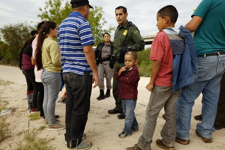 Ely Fernandez is questioned by border patrol agent Robert Rodriguez after being detained for crossing the border illegally with his son 5-year-old Bryan, center, on March 15, 2018 in McAllen, Texas.
