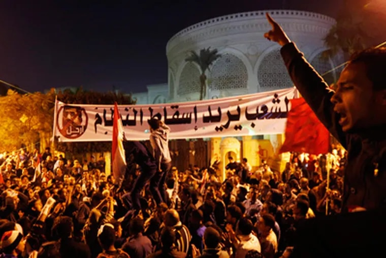 """Protesters chant slogans during a demonstration in front of the presidential palace in Cairo, Egypt, Sunday, Dec. 9, 2012.  Egypt's liberal opposition called for more protests Sunday, seeking to keep up the momentum of its street campaign after the president made a partial concession overnight but refused its main demand he rescind a draft constitution going to a referendum on Dec. 15. Arabic on the banner, background, reads, """"the people want to end the regime.""""(AP Photo/Petr David Josek)"""