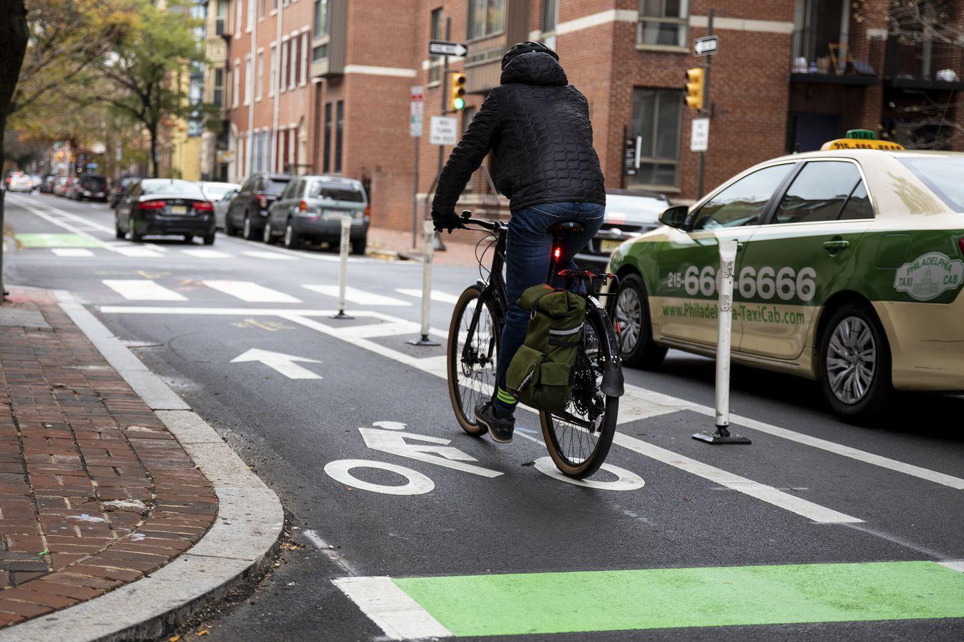 A biker rides along the sectioned bike lane along Spruce Street near Ninth Street on Wednesday, Nov. 20, 2019.