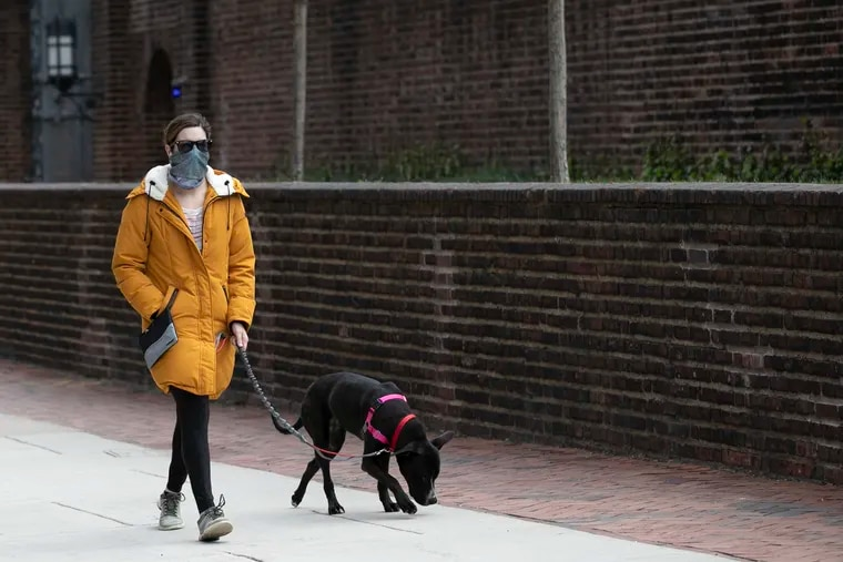 A pedestrian wears a protective face mask out in front of the Penn Museum in Philadelphia on Friday. Gov. Tom Wolf is now urging Pennsylvanians to wear masks in public due to the spread of the coronavirus.