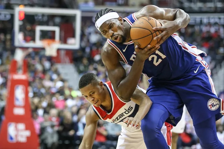 Sixers' Joel Embiid grabs the loose ball from Wizards' Tim Frazier during the 3rd quarter at the Capital One Arena in Washington, DC, Wednesday, October 18, 2017. Wizards beat the Sixers 120-115. STEVEN M. FALK / Staff Photographer