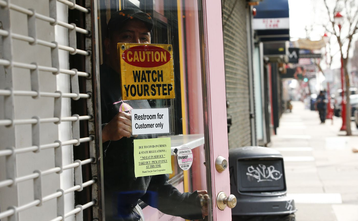 A employee at Ishkabibble's, along South Street, peers outside the restaurant on Friday, March 20, 2020. The coronavirus has shut down eat-in food service at restaurants.