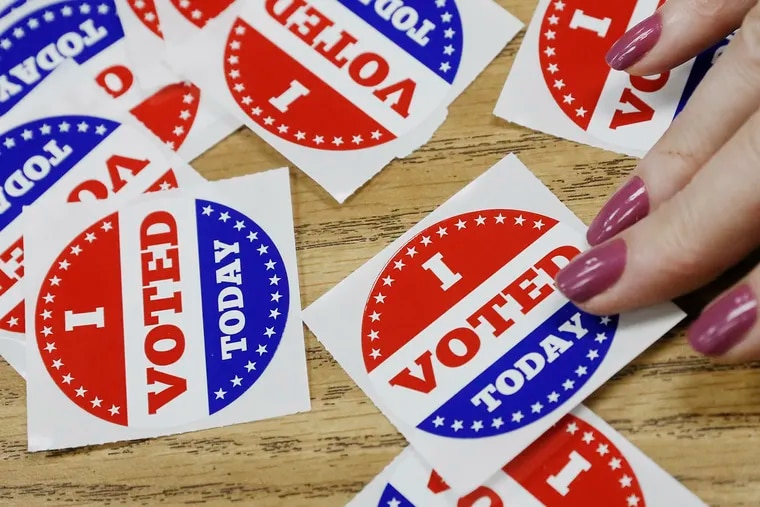 """Poll workers hand out """"I VOTED"""" stickers during election day voting at the Washington Township Board of Education building in Washington Township, Gloucester County on November 6, 2018."""