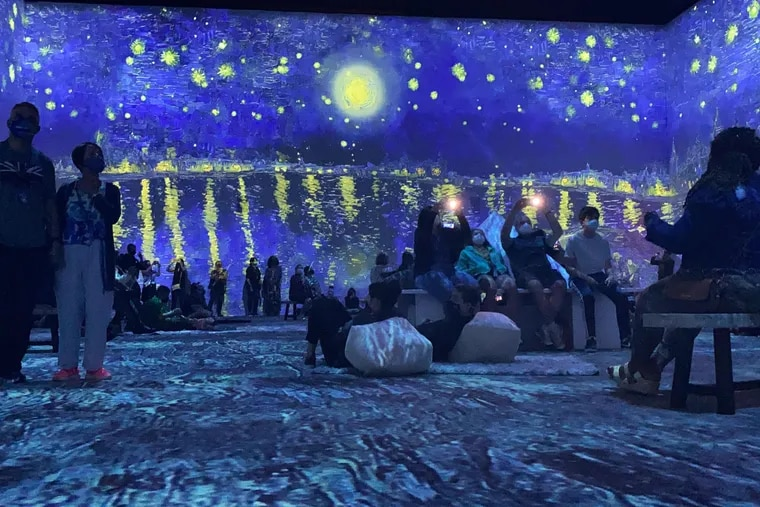 """Visitors to """"Van Gogh: The Immersive Experience"""" at the Tower Theater in Upper Darby are enveloped in Vincent Van Gogh's painting, """"Starry Night Over the Rhône."""""""