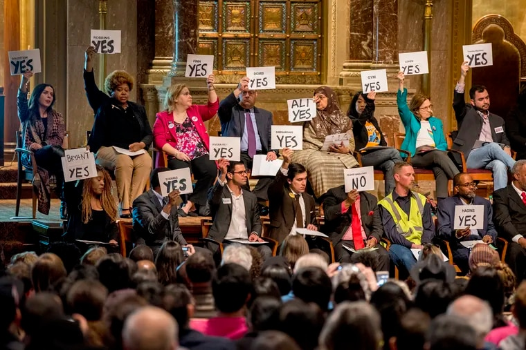Candidates for at-large City Council seats hold signs indicating their positions on questions posed during a forum at Congregation Rodeph Shalom in Philadelphia on Sunday, March 24, 2019.