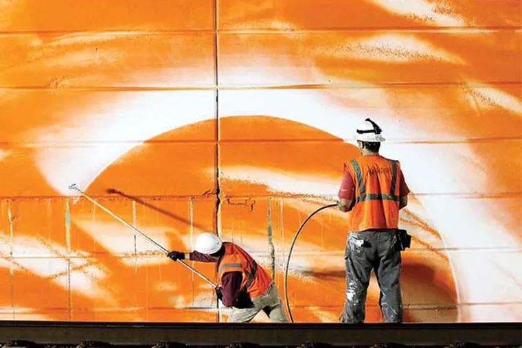 Mural Arts Project artist Tom Walton (left) sprays paint on the walls as Staff Artist Nathaniel Lee assist, along Amtrak Northeast Corridor route, near 30th Street Station on Sunday, May 11, 2014.  ( Yong Kim / Staff Photographer )