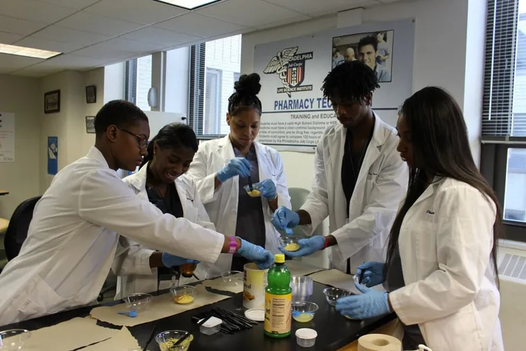 Philadelphia Job Corps pharmacy tech students, Alana Miller, left to right, Princess Wimberly, Kiara Mackie, Daniel Bierre and Achante Holmes mix ingredients to make a face mask, using similar techniques to what is done in a pharmacy. Job Corps is partnering with CVS and Kensington Health Sciences Academy to create a pharmacy technician apprenticeship program