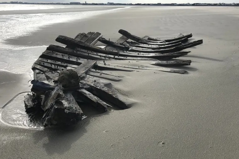 The remains of a shipwreck that dates to the late 1880s are uncovered by recent weather on a beach in Stone Harbor, NJ.