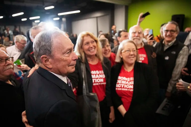 Democratic presidential candidate and former New York City Mayor Michael Bloomberg, left, has a photo taken with members of Moms Demand Action for Gun Sense in America at a campaign event Wednesday, Feb. 5, 2020, in Providence, R.I.