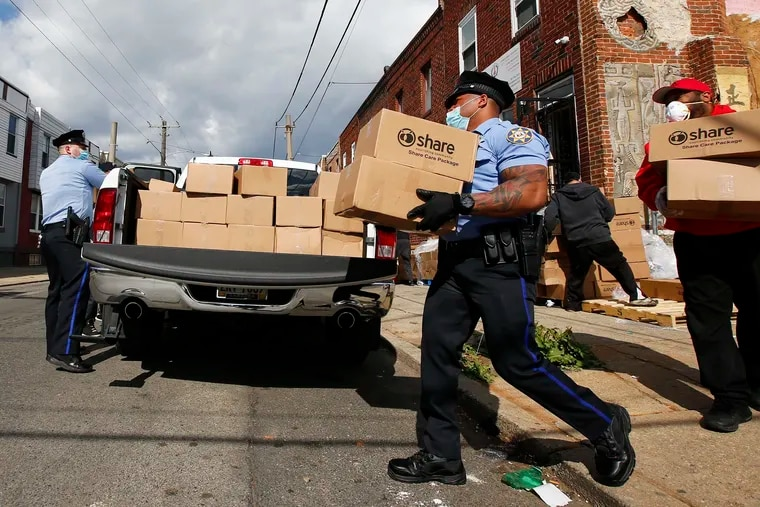 Philadelphia Sheriff Officers and volunteers load boxes of food, bound for North Philadelphia residents, from the Share Food Program distributed at the Young Chances Foundation in the Point Breeze neighborhood of Philadelphia in April.