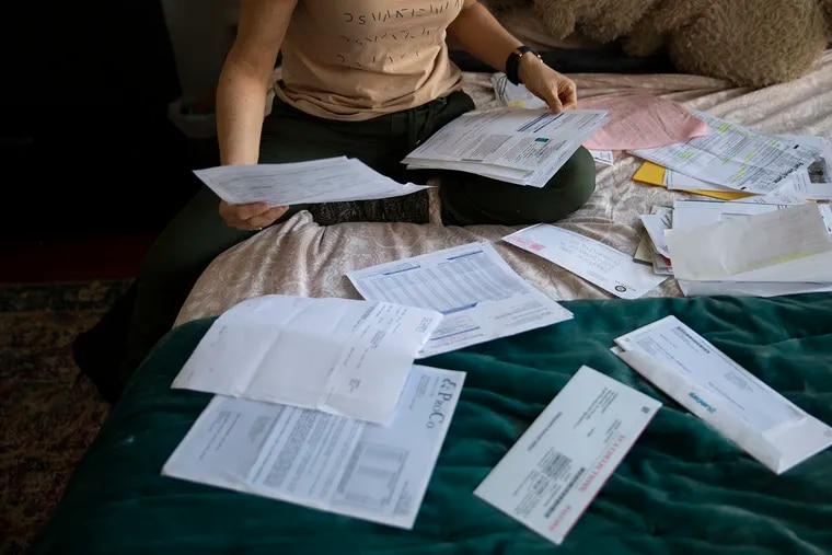 Stephanie Sena, 39, sits on her bed surrounded by a folder full of medical bills from a foot amputation she had last fall on Thursday, April 04, 2019. Sena is an adjunct professor at Villanova University with $20,000 in medical debt. Sena needed to come up with $1,900 up-front for an amputation after learning her health plan wasn't real insurance.
