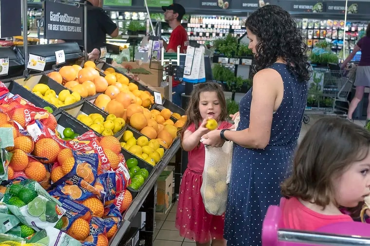 Mother and daughter, 5, pick lemons from a bin at their local Giant supermarket as the 3-year-old waits in the shopping cart.
