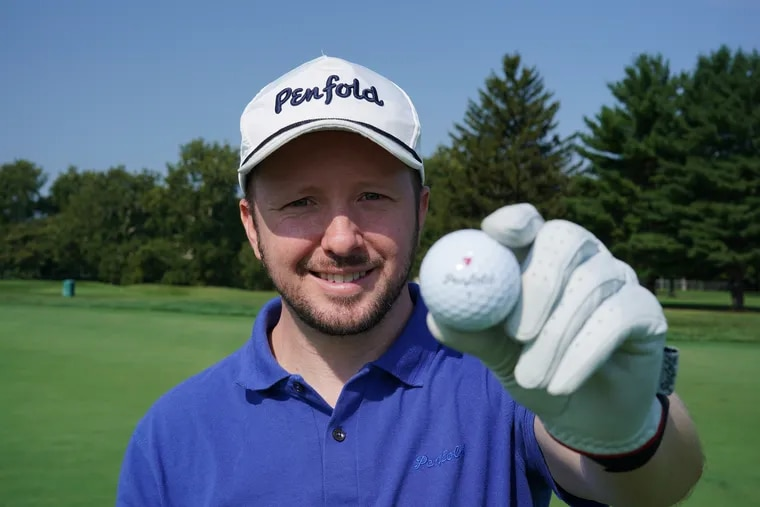 Gavin Perrett holds up a Penfold golf ball on the practice green at the LuLu Country Club in Glenside, Pa.