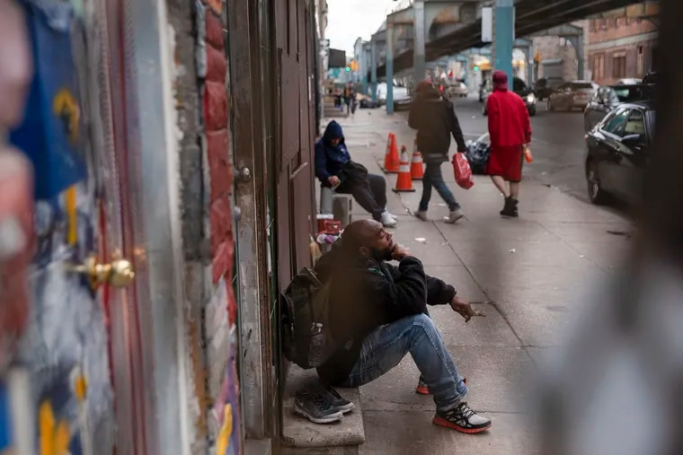 People sits outside Prevention Point in Kensington, considered the epicenter of Philadelphia's opioid crisis, though overdose deaths occur throughout the city.