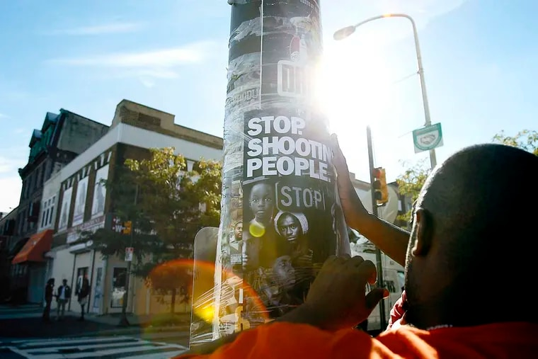 Terry Starks of Philadelphia Ceasefire tapes a poster to a pole near the scene of the subway shooting Wednesday, September 19, 2012. At least one teen was arrested. DAVID MAIALETTI / Staff Photographer