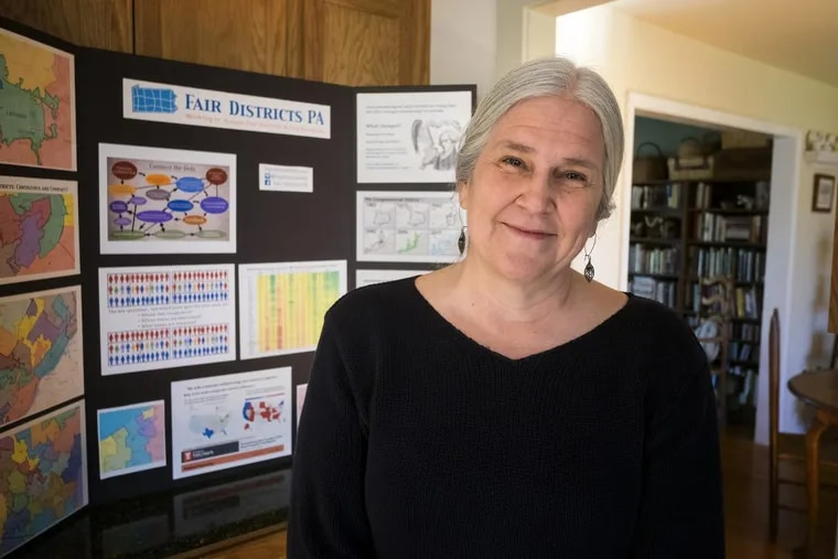 Carol Kuniholm, co-founder and chair of Fair Districts PA, stands in hereExton kitchen with a display she uses in meetings to show how voting districts have been gerrymandered.