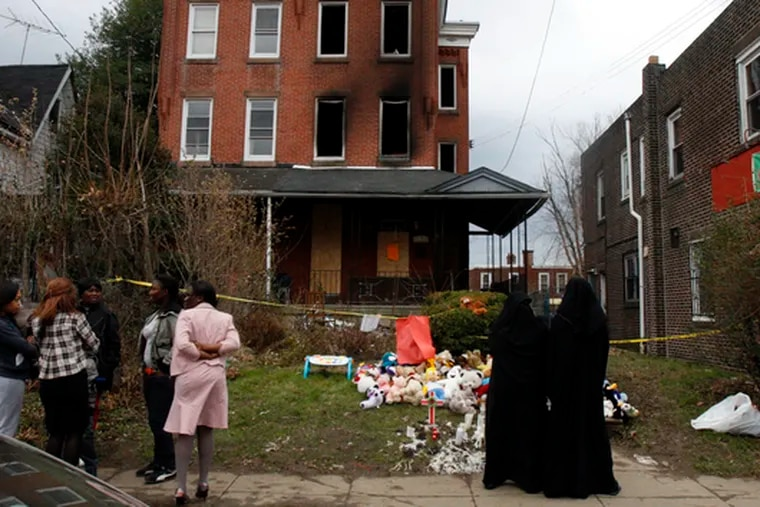 Neighbors mingle in front of the house in Southwest Philadelphia where seven people died in a fire Friday. Officials suspect a mishandled kerosene heater started the blaze.