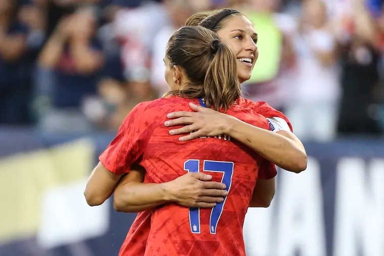 Delran native Carli Lloyd hugs teammate Tobin Heath during the first half. Lloyd recently made waves when she drilled a long field goal at Eagles practice, prompting teams to reach out about kicking in the NFL.