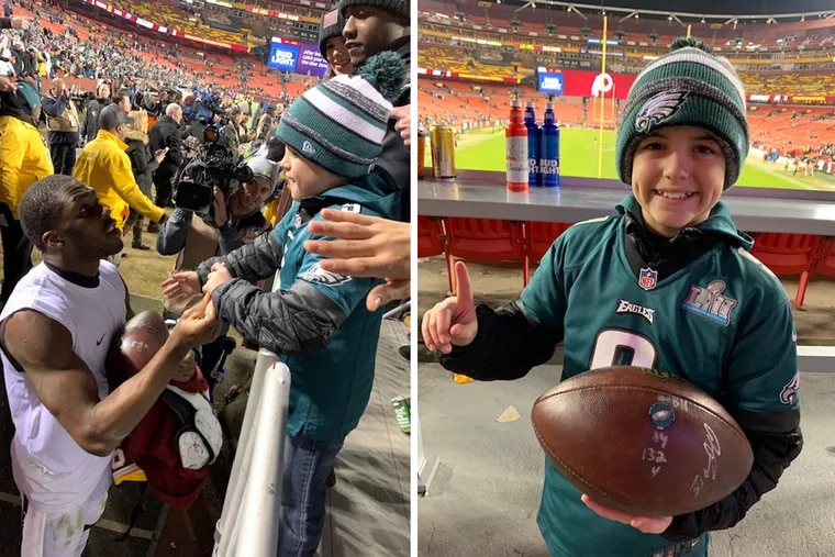 Eagles wide receiver Nelson Agholor signs a football for Cohen Zechman, a 10-year-old Eagles fan who went viral for giving Nate Sudfeld the football from the quarterback's first touchdown pass back.