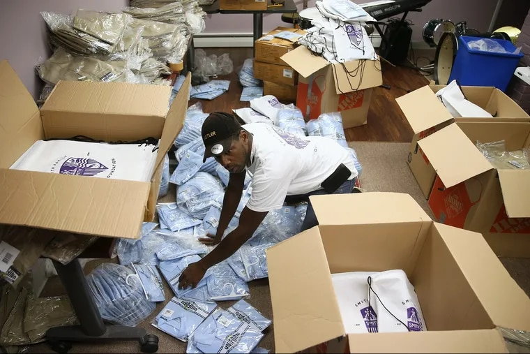 Volunteer Mark Sessoms packs school uniforms into drawstring bags at the Smith Family Foundation office in Trenton, N.J. The foundation is giving away 400 free uniforms to Parker Elementary School students. The Smith family established the foundation after winning the $429 million Powerball jackpot in 2016. TIM TAI / Staff Photographer