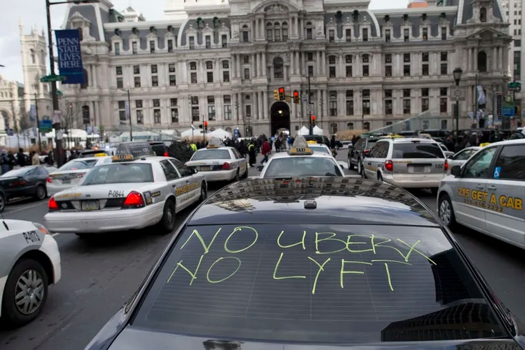 In this February 2016 file photo, taxis and Uber Black cars — one with a message — park in front of City Hall as their drivers demand better regulation of Uber X.