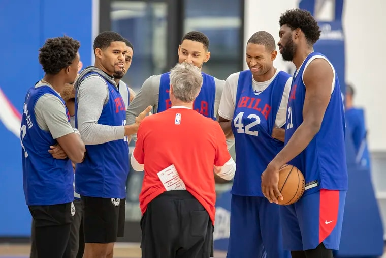 Sixers head coach Brett Brown chatting with some of his players last October at the team's practice facility.