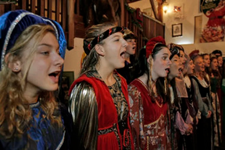 The Madrigal Singers of Haddonfield Memorial High School lift their voices at the Camden Rotary Club's holiday dinner at Hollings Head,in Clarksboro. This group sports full period costumes and will hold its annual Madrigal Dessert Theatre next week.