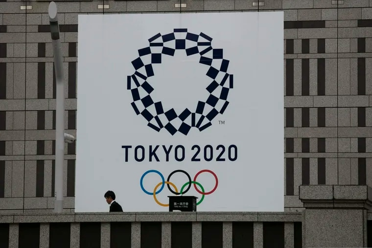 A man walks past a large banner promoting the 2020 Olympics in Tokyo.