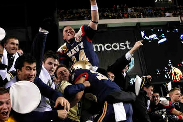Navy players join fans in celebrating the Midshipmen's eighth victory in a row against Army in the 110-game football rivalry. For the third year in a row Navy prevented Army from scoring a touchdown.
