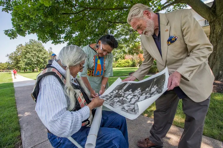 Mark Soldier Wolf, left, and his daughter, Yufna Soldier Wolf, center, look over a historical photo on on Aug. 9, 2017 as they tour the Carlisle Barracks, which once served as the Carlisle Indian Industrial School in Pennsylvania. Many non-Indigenous Americans have the misperception that Native Americans are only part of the United States' past, not its present.