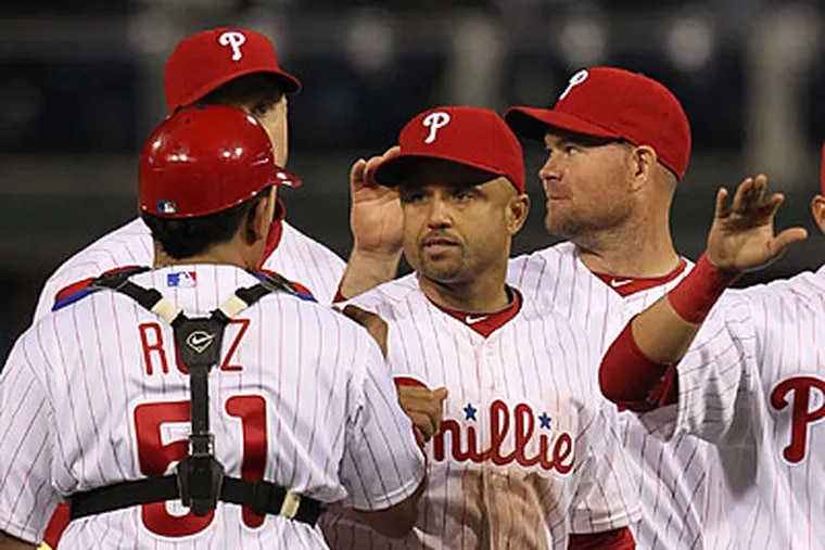 Placido Polanco leads the Phillies' celebrations after the final out of Monday's win. (David M Warren/Staff Photographer)