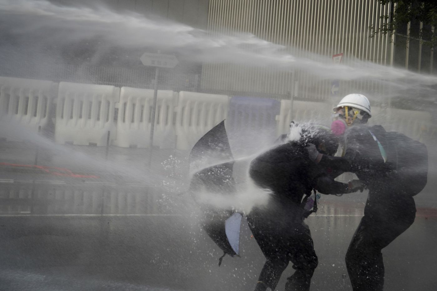 Hong Kong police disperse protests with tear gas and water cannon as unrest enters its 15th week