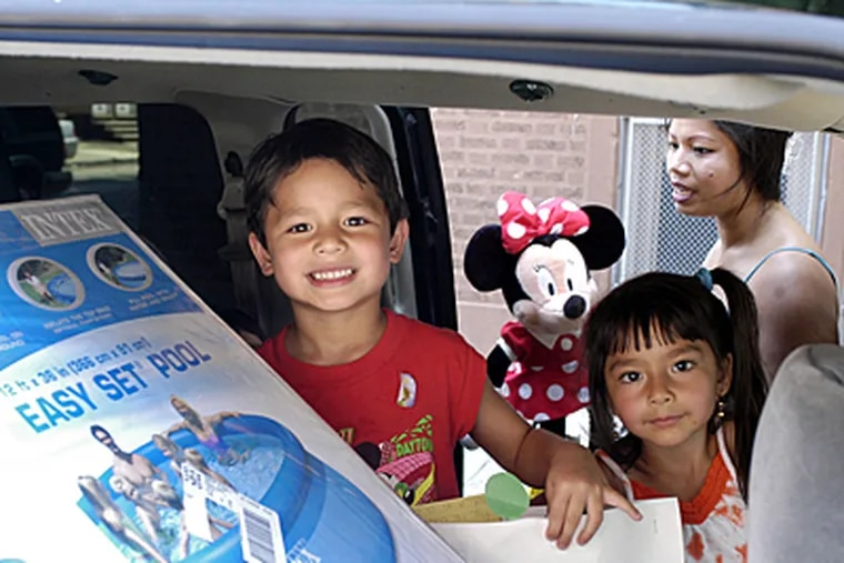 Vince Cammisa, 5, (left) and his sister Isabella Cammisa, 3, (right) join a new  pool in the back of the minivan as mom Sinuon Cammisa picks them at Jackson Elem. School in South Phila. yesterday.
