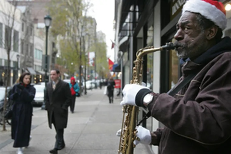 Knoel Scott plays the saxophone on Walnut Street near 18th Street. The settlement of a flutist's lawsuit has revived debate over how the city should handle street performers.