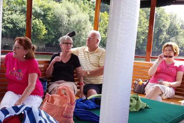 Pat Adams (from left), Jane Messick, Bob Foster, and Jeanne Maxwell, on a boat ride on the Schuylkill, are members of East Falls Village, an online-organized group of retirees. (MARY FLOURNOY)