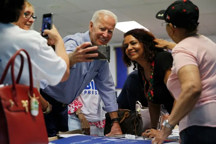 In this July 20, 2019, file photo, former Vice President and Democratic presidential candidate Joe Biden takes a selfie with a supporter during a campaign event at an electrical workers union hall in Las Vegas. More than traditional markers of electability like name recognition, fundraising ability or charisma, the path to the Democratic nomination runs through black voters.
